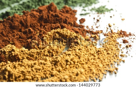 three-color powder spices blend on white surface - stock photo