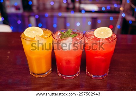 three colored bright cocktail with mint and lemon on the wooden bar counter - stock photo