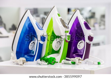 three colored electric irons at retail store shelf, defocused background - stock photo