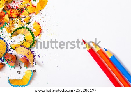three colored pencils and shavings on white background with copy space - stock photo