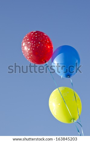 three colorful balloons on blue summer sky. Holiday background - stock photo