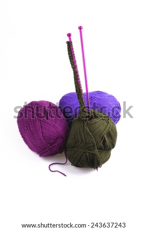 Three colorful balls of wool in charcoal, purple and blue with knitting needles onto which the first stitches have been cast, over white - stock photo