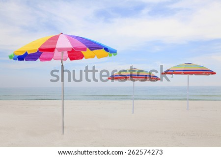 Three Colorful Beach Umbrellas on a White Sand Florida Beach - stock photo