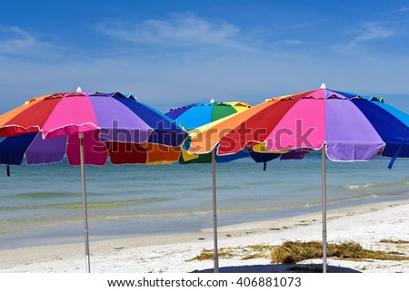 Three Colorful Beach Umbrellas with the Ocean and Sky in the Background - stock photo