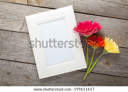 Three colorful gerbera flowers and photo frame on wooden table - stock photo
