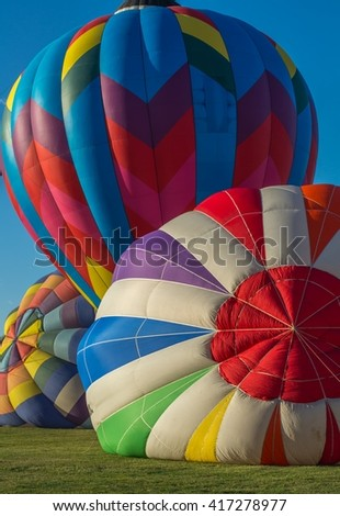 Three colorful  hot air balloons inflating before launch at balloon festival. - stock photo
