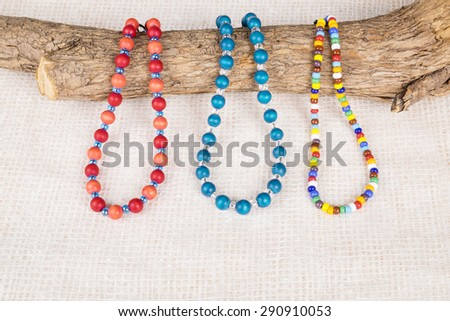 Three Colorful Necklaces Resting on a Tree Branch Shot in Studio - stock photo