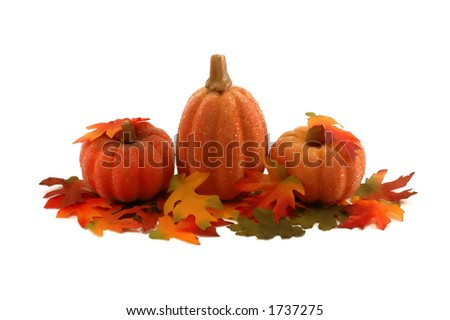 Three colorful pumpkins and autumn leafs - stock photo