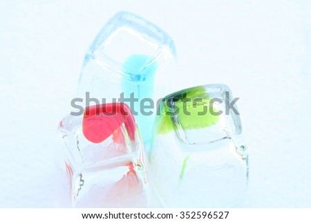 Three colorful shot glasses in rectangular shape, arranged in various formation with white background. - stock photo