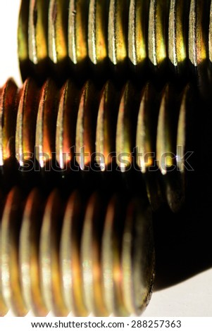 Three colorful steel bolts lying in parallel showing sharp grooves. Product photography. Industrial photography. - stock photo