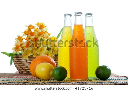 Three colorful wet bottles with tropical drinks with some fruits next to the on white background - stock photo