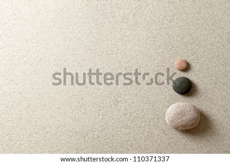 Three colorful zen stones at right side of sand background - stock photo