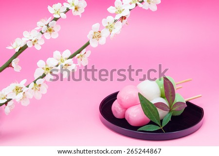 Three colors Japanese dumpling with white blossom of plum - stock photo