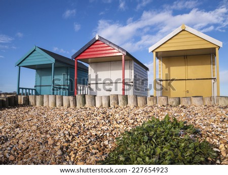 Three colourful beach huts - stock photo