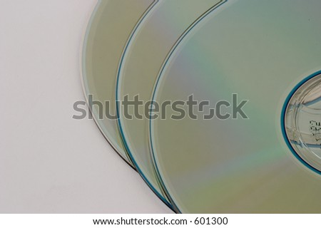 Three compact discs laid out on a white surface, partially stacked. - stock photo