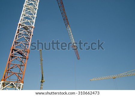 Three construction cranes Construction site and cranes - stock photo