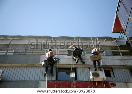 three construction workers working on house - stock photo