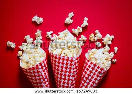 Three containers full on popcorn on a red background - stock photo