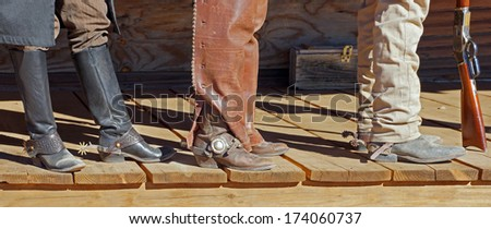 Three cowboys stand on the porch showing their dusty boots and spurs - stock photo