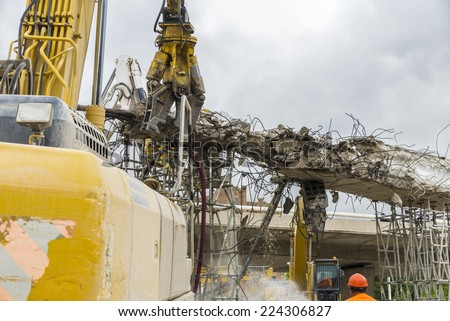 Three cranes breaking down a bridge in square Les Glories, Barcelona. - stock photo