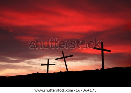 Three crosses on a hill at sunset - stock photo