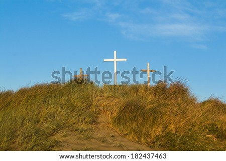 Three crosses on a hill with a pathway leading up to them - stock photo