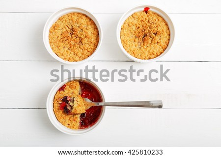 Three crumbles with raspberries, gooseberries, blackberries and cinnamon. English dessert in a white ceramic mold for baking on white wooden table. Top view. - stock photo