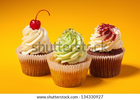 three cupcakes isolated on orange background - stock photo