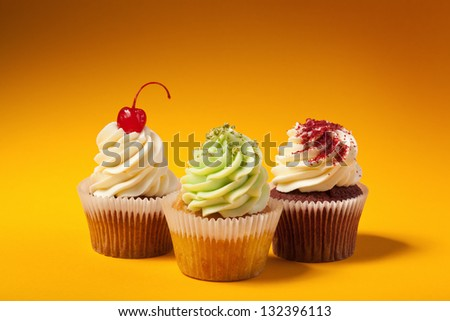 three cupcakes isolated on orange background with copyspace - stock photo