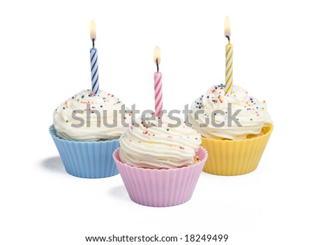 Three cupcakes with candle on white background - stock photo