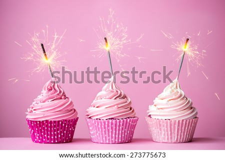 Three cupcakes with pink frosting and sparklers - stock photo