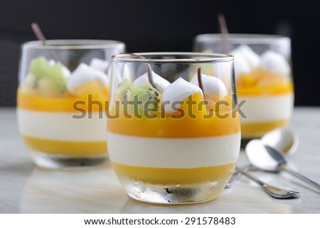three cups of mango panna cotta - stock photo