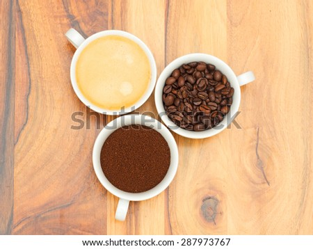 Three cups with coffee, coffee beans and ground coffee on wooden table - stock photo