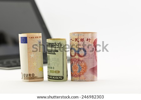Three currencies, euro, United States dollar, and Chinese yuan, placed before tablet and keyboard.  - stock photo
