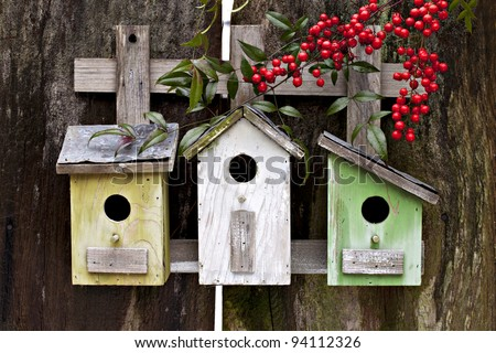 Three cute birdhouses with winter berries and old rustic wooden fence - stock photo