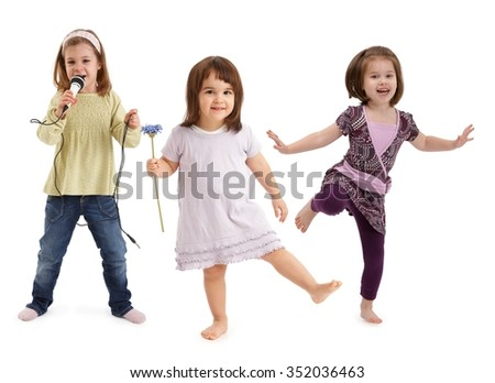Three cute little girls dancing, singing to microphone, having fun over white background. - stock photo