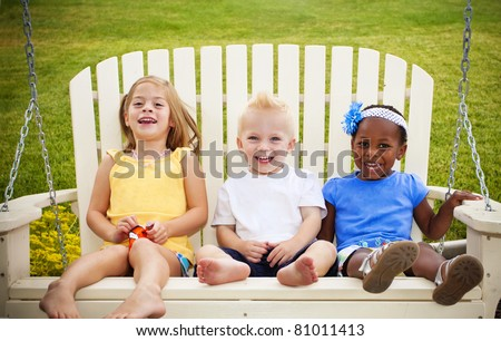 Three cute little kids sitting together on a porch swing - stock photo