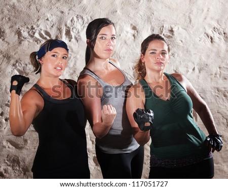 Three cute muscular women flexing their arms - stock photo