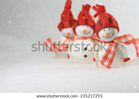 Three cute smiling  snowmen with the focus on the first one, with copy space - stock photo