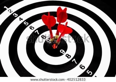 Three darts hitting the center - stock photo