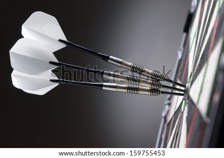 Three darts in bullseye of dartboard - stock photo