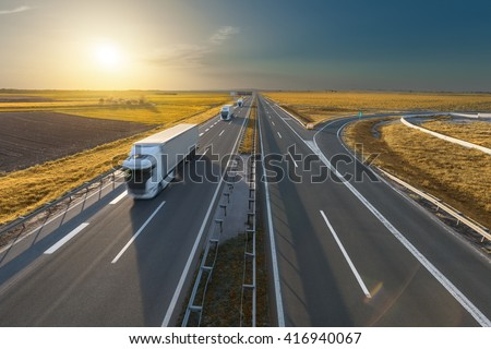 Three delivery trucks driving towards the sun. Fast blurred motion driving on the freeway in beautiful autumn scenery. Freight scene on the motorway near Belgrade, Serbia. - stock photo