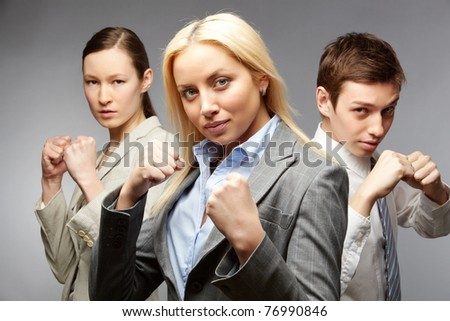 Three determined businesspeople in defense pose - stock photo