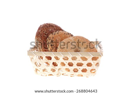 three different bagels in basket isolated over white background - stock photo