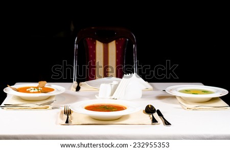 Three different bowls of hot vegetable soup served at table with a creamy pumpkin soup, vegetable minestrone and legume soup with coriander - stock photo