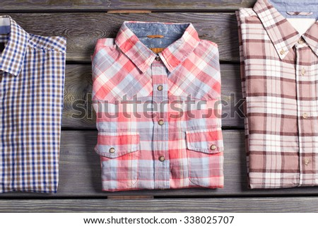Three different checked shirts on wooden background. Youth men's shirts. - stock photo