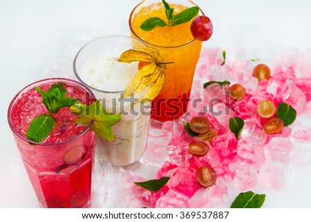 Three different cold drinks Fresh juice mix Three of fruit cocktails. Different cocktails with mint and ice. Alcoholic fruity cocktails isolated on white. - stock photo