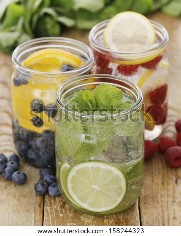 Three different cold drinks with straws on a wooden table - stock photo