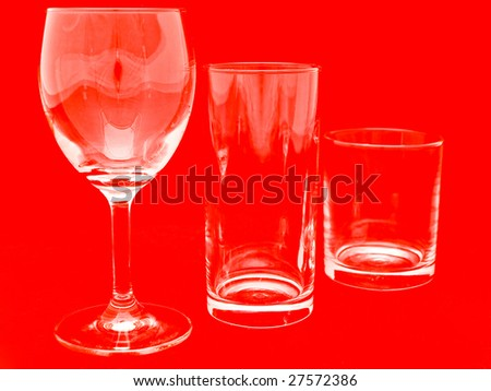 three different glasses over the red background - stock photo