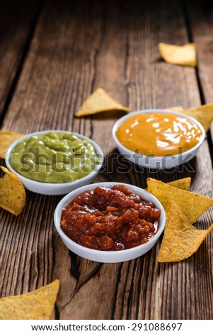 Three different nacho dips (Salsa, Cheese and Guacamole) - stock photo